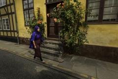Foto: Steffen Jensen | Yasmins blå og lilla tøj gør sig fint med Rudkøbings gamle huses gule puds.